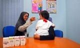 Seorang perawat tengah memberikan cairan Anti Retroviral Virus (ARV) sebagai obat memperlambat perkembangan virus kepada anak dengan HIV/AIDS.