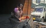 Seorang perempuan India mengumpulkan sisa kacang-kacangan dari sebuah truk sembako di Gauhati, India, Rabu (8/1). Laporan baru Oxfam menunjukkan ekonomi dunia memicu ketimpangan yang seksis.