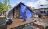 Seorang perempuan korban gempa berada dekat tenda yang dibangun diatas bekas rumahnya yang roboh akibat gempa di Desa Dopang, Kecamatan Gunungsari, Lombok Barat, NTB, Selasa (26/3/2019).