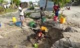 Seorang perempuan mengambil air dari sumber yang tidak terlindungi di Beira, Mozambik, Ahad (31/3). Kasus kolera melonjak di Mozambik usai badai Idai melanda.
