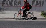 Seorang pesepeda melintasi grafiti berbahasa Spanyol di jalan di Buenos Aires, Argentina, Selasa (4/9). Grafiti tersebut berarti 'Pergilah IMF'. Beberapa pekan terakhir, krisis Argentina meningkat dan memaksa negara tersebut berutang ke IMF.