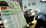 Seorang petugas dari biro perjalanan haji dan umrah (kiri) menerangkan proses pemberangkatan umrah kepada calon jamaah.