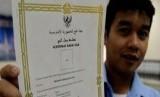 Seorang petugas haji memperlihatkan sertifikat badal haji yang telah siap diberikan kepada keluarga jamaah haji Indonesia