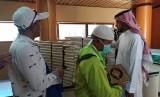 Seorang petugas memberikan Al-Quran kepada jamaah haji yang berkunjung ke Pusat Percetakan Al-Quran di Madinah, Selasa (16/7). Al-Quran dicetak di tempat ini sebanyak 18 juta eksemplar dan disebar ke 76 negara di dunia.