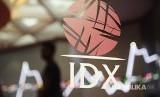 Seorang pria melintasi layar elektronik pergerakan saham di Bursa Efek Indonesia, Jakarta, Rabu (31/1). Indeks Harga Saham Gabungan (IHSG) ditutup menguat 30 poin atau 0,46 persen ke 6.605.