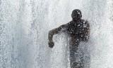 Seorang pria mendinginkan diri di tengah cuaca panas ekstrem Eropa di air mancur taman Lustgartendi Berlin, Jerman, Rabu (26/6).