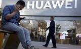 Seorang pria menggunakan ponselnya di depan toko Huawei di Beijing, Cina, Senin (20/5).