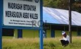 Madrasah di Papua Minim Guru PNS, Kemenag: Jawa Juga Minim. Seorang Siswa membaca buku di halaman sekolah setelah melakukan kegiatan belajar mengajar di Madrasah Ibtidaiyah Yapis Walesi, Wamena, Kabupaten Jayawijaya, Papua.