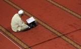 Seorang umat Muslim membaca Alquran usai melaksanakan shalat dhuha (ilustrasi).