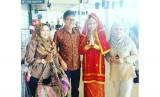Seorang  wanita berpakaian adat memberikan selendang sarung dan anyaman khas minang kepada para wisatawan yang datang di Bandara Internasional Minangkabau.