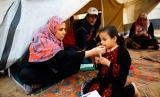 Seorang wanita Palestina menyuapkan makanan kepada putrinya di sebuah tenda dekat lokasi bentrokan antara demonstran Palestina dan pasukan Israel menyusul protes di sepanjang perbatasan dengan Israel, sebelah timur Kota Gaza, pada 3 April 2018.