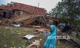 Seorang warga melintas di depan rumah yang roboh akibat angin puting beliung.