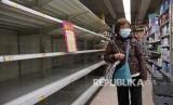 Seorang warga melintasi rak tisu yang kosong di sebuah supermarket di Hong Kong. Pemerintah Hong Kong siapkan dana untuk atasi kesulitan ekonomi akibat Corona. Ilustrasi.