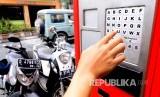 Seorang warga membayar parkir di tempat mesin smartparking (Ilustrasi)