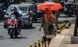 Seorang warga menggunakan payung saat cuaca terik. Foto (Ilustrasi).