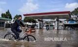 Seorang warga menggunakan sepeda melintasi genangan banjir di Jalan Raya Andir, Baleendah, Kabupaten Bandung, Jumat (24/1).