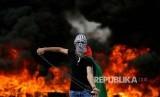 Seorang warga Palestina membawa ketapel pada peringatan 70 tahun hari Nakba (hari di mana warga Palestina diusir secara besar-besaran oleh Israel) di Ramallah, Tepi Barat Palestina, Selasa (15/5)