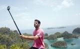 Seorang wisatawan mancanegara berfoto diri dengan latar belakang pemandangan di Pianemo, Raja Ampat, Papua Barat, Senin (2/11). Untuk menempuh menuju lokasi tersebut dari Waigeo di Waisai (Ibu Kota Kabupaten Raja Ampat) adalah dua jam perjalanan.