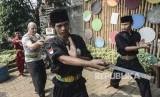Seorang wisatawan mancanegara (kedua kiri) berlatih Pencak Silat Golok Terbang di Situ Rawa Gede, Bekasi, Jawa Barat, Ahad (8/9/2019).