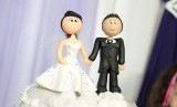 Sepasang suami istri tergambar di atas kue perkawinan.