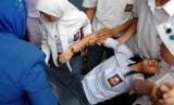 Manfaat ruqyah tidak hanya sebatas mengusir jin dan kesurupan. Foto siswa kesurupan. (ilustrasi)
