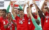 Striker Bayern Muenchen, Robert Lewandowski (tengah) mengangkat trofi Bundesliga musim 2018/2019.