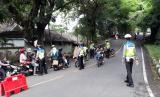 Tampak petugas kepolisian di Sukabumi meminta sejumlah pengendara motor untuk putar balik  guna menekan angka penyebaran Covid-19