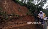 Tentara membantu salah satu warga berjalan saat evakuasi longsor di Jalur Utama Puncak, Bogor, Jawa Barat, Senin (5/2).