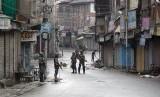 Tentara paramiliter India berjaga di jalanan yang sepi saat jam malam di Srinagar, Kashmir yang dikuasai India, Kamis (8/8).