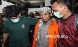 Terdakwa kasus dugaan teror bom Thamrin Aman Abdurrahman alias Oman (tengah) digiring petugas seusai menjalani sidang perdana kasus terorisme dengan agenda pembacaan dakwaan di PN Jakarta Selatan, Jakarta, Kamis (15/2).