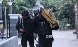 Tim Densus 88 membawa barang bukti saat penggeledahan usai penangkapan terduga teroris di Jemaras, Klangenan, Kab. Cirebon, Jawa Barat, Kamis (17/5).