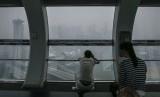 Turis asal Cina melihat pemandangan Singapura yang tertutup kabut asap dari salah satu kabin Singapore Flyer (23/10).