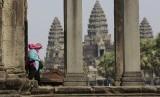 Turis melewati kuil Angkor Wat di Kamboja.