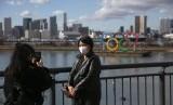 Turis mengenakan masker berfoto dengan latar logo Olimpiade di Odaiba, Tokyo, Jepang, Rabu (29/1). Jepang telah mengevakuasi warganya dari China yang terkunci akibat virus corona.
