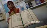 Seorang wanita melihat Terjemahan Alquran ke bahasa daerah saat peluncurannya di Kemenag, Jakarta, Senin (19/12).
