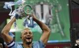 Vincent Kompany mengangkat trofi Piala Liga Inggris.