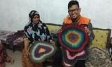 Wak Yus bersama Fasilitator Rumah Zakat Fauzi menunjukkan keset karya Wak Yus.