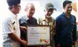 Wakil Wali Kota Malang Sutiaji (kiri) menyerahkan bantuan Bedah Rumah dari Rumah Zakat secara simbolik kepada Warisan (52 tahun), warga tidak mampu, di Kelurahan Purwantoro, Kecamatan Blimbing, Kota Malang, Selasa (21/3).