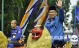 Wali Kota Bandung Ridwan Kamil diarak-arak dengan sisingaan saat menghadiri acara deklarasi dukungan Partai Nasdem untuk Ridwan Kamil sebagai calon Gubernur Jawa Barat di Lapangan Tegalega, Kota Bandung, Ahad (19/3).