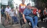 Walikota Bogor Bima Arya (tengah) bersama warga penyandang disabilitas mengikuti jalan sehat melewati fasilitas publik ramah disabilitas di pedestrian Kebun Raya Bogor, jalan Juanda, Kota Bogor, Jawa Barat, Minggu (8/1).