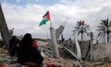 Wanita Palestina berkumpul di dekat rumahnya yang hancur di selatan Jalur Gaza, Senin (13/1). Memasuki musim dingin warga Palestina harus berjuang melawan hawa dingin yang akan mecapai puncaknya pada bulan ini.