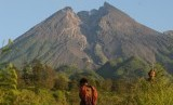 Warga beraktivitas dengan berlatar belakang Gunung Merapi.
