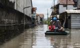 Warga berjalan menembus jalan yang terendam luapan air Sungai Citarum, di Desa Deyeuhkolot, Kabupaten Bandung, Jawa Barat, Rabu (22/11).