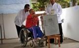 Penyandang disabilitas dibantu petugas untuk menggunakan hak suaranya. (ilustrasi)
