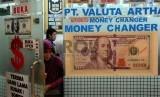 Warga melakukan penukaran uang dollar di Money Changer disalah satu pusat perbelanjaan Jakarta, Rabu (12/8).