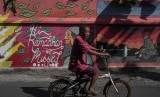 Warga melintas di depan mural bertema ramadan di kampung wisata batik Laweyan, Solo, Jawa Tengah, Rabu (24/5). (Ilustrasi)