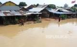 Warga melintas di depan tempat tinggalnya yang terendam banjir akibat meluapnya sungai Cisadane di kawasan Karawaci, Tangerang, Banten, Jumat (26/4/2019).