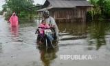 Warga melintas di jalan yang terdampak banjir di Desa Setrokalangan, Kaliwungu, Kudus, Jawa Tengah, Senin (24/2/2020).