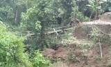 Warga melintas di jembatan darurat yang dibangun menuju wilayah yang terisolasi di dua desa di Kecamatan Cisayong dan Sukaratu, Kabupaten Tasikmalaya, Jumat (28/2) sore.
