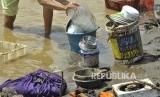 Warga membersihkan barang-barang pascabanjir bandang di Tarogong Kidul, Kabupaten Garut.